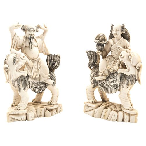 Pair of Figures on Foo Dogs, Asia, Ca. 1900, Carved and inked ivory with floral motifs.