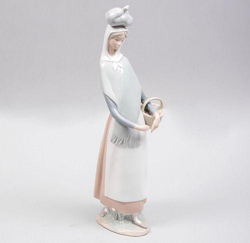 Dama con canasta. España. Ca 1970. Elaborada en porcelana Lladró. Acabado brillante.