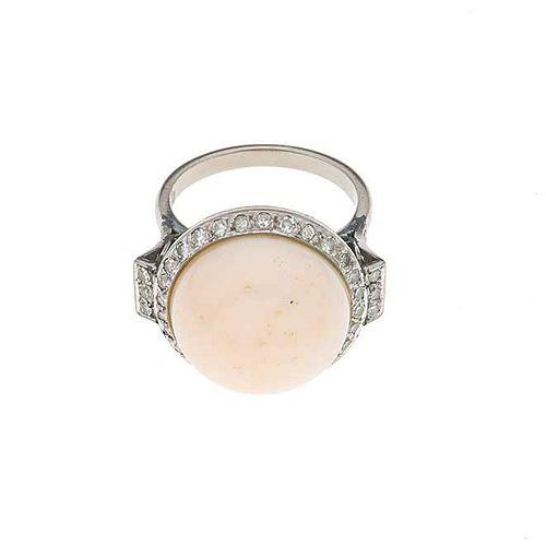 Anillo vintage con coral y diamantes en plata paladio. 1 coral corte cabujón color rosa palido de 12 mm. 51 diamantes.