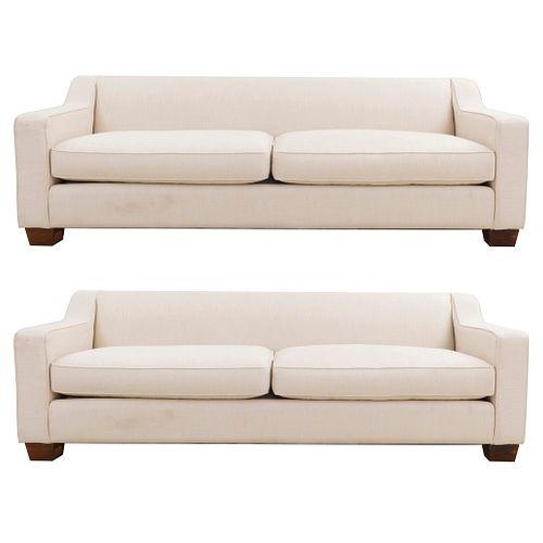 Par de sofás de 3 plazas. Siglo XX. En talla de madera. Con respaldos cerrados y asientos con cojines en tapicería color beige.