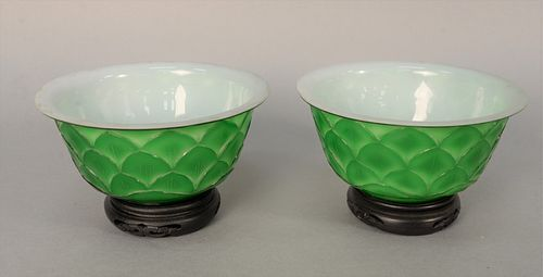 Pair of Chinese Peking Overlay Glass Bowls having green exterior carved with lotus petals and white interior glass on carved wood st...