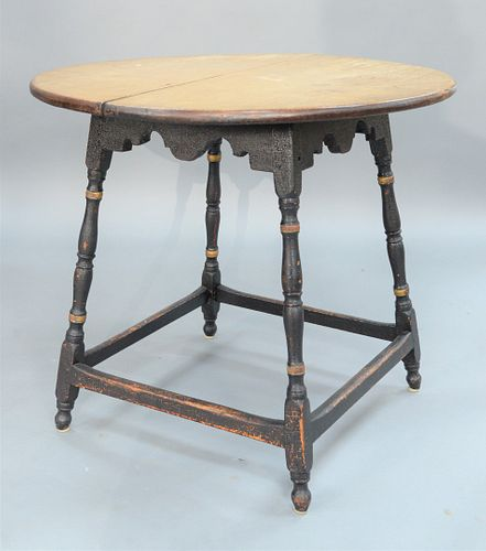 Tavern Table having round maple top on over scalloped apron set on turned splayed legs with box stretcher on round feet, in old black paint with gold