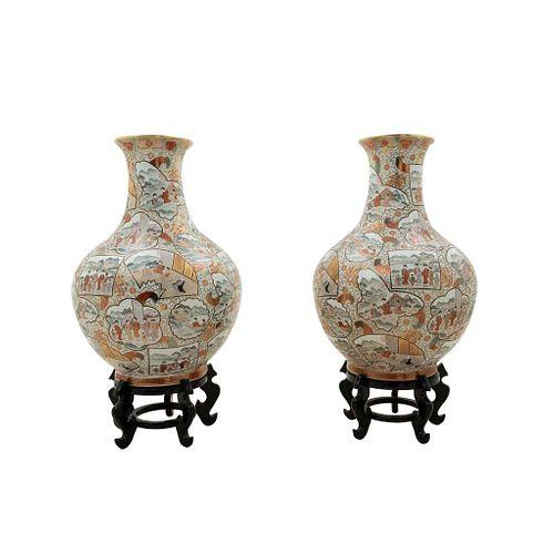 Par de jarrones. Japón. Siglo XX. Elaborado en porcelana policromada. Con bases de madera.