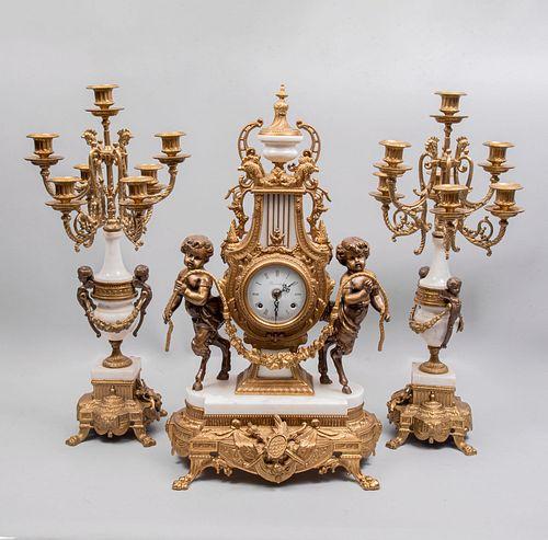 Guarnición. Italia. S.XX. Marcado Imperial en cáratula. En metal dorado y mármol. Consta de: Par de candelabros y reloj de chimenea.