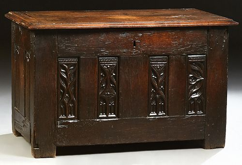 French Provincial Carved Oak Coffer, 19th c., the stepped slanted edge top over four relief Gothic carved panels, flanked by linen f..