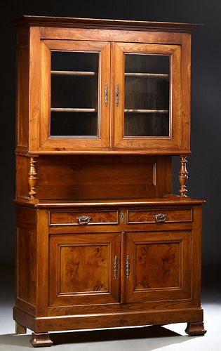 French Louis Philippe Carved Elm Buffet a Deux Corps, 19th c., the stepped crown over double glazed doors on turned tapered supports...
