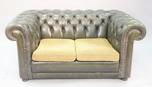 "A Chesterfield style green tufted leather loveseat with upholstered cushions, 28"" x 60-1/2"" x 35""."