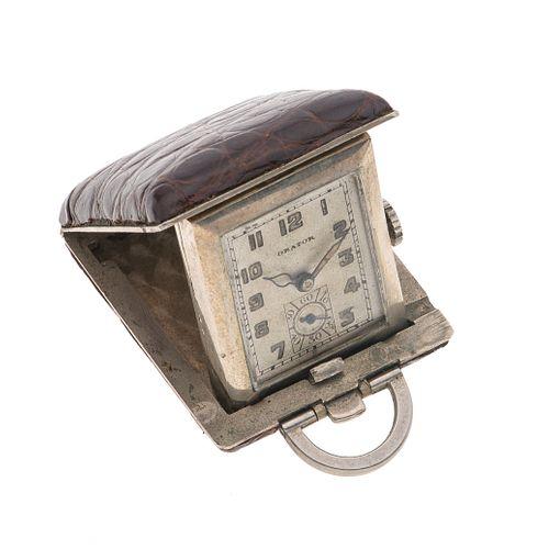 Reloj de viaje marca Orator. Movimiento manual. Caja rectangular en metal base con cubierta de piel color café. Carátula color gris.