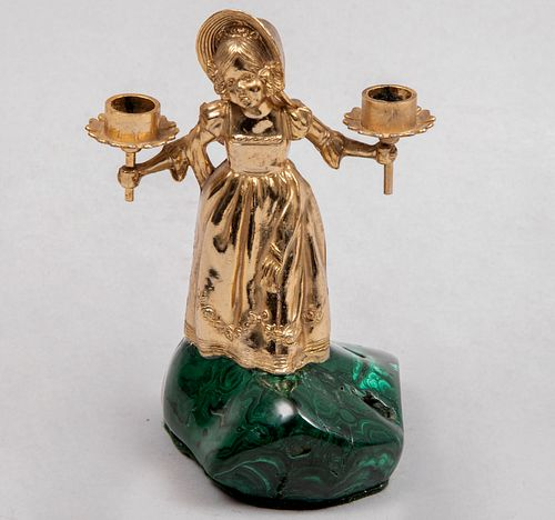 Candelabro. Siglo XX. Diseño a manera de niña. Fundición en bronce. Para 2 luces. Con arandelas florales y base de malaquita.
