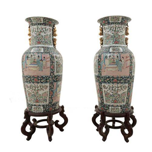 Par de jarrones. China. Siglo XX. Estilo Familia Rosa. Elaborados en porcelana. Con bases de madera. 93 cm de altura