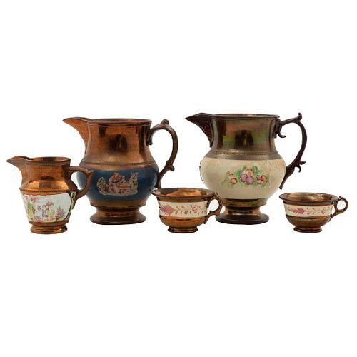 """Lote de 5 piezas. Siglo XIX. Elaborados en cerámica con esmalte """"Copper Luster"""". Consta de: cremera, 2 tazas y 2 jarras."""
