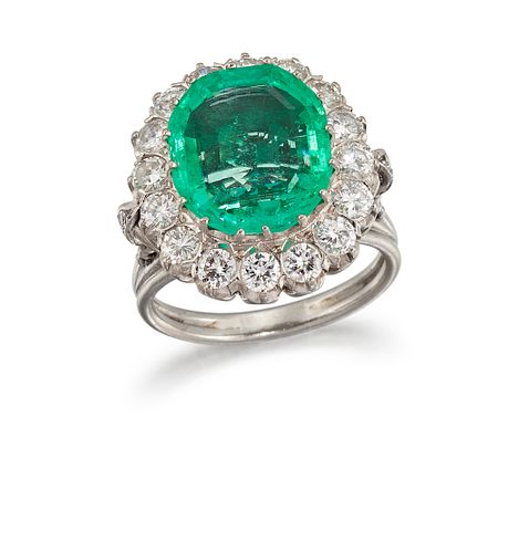 AN EMERALD AND DIAMOND CLUSTER RING  Centred by a claw-set