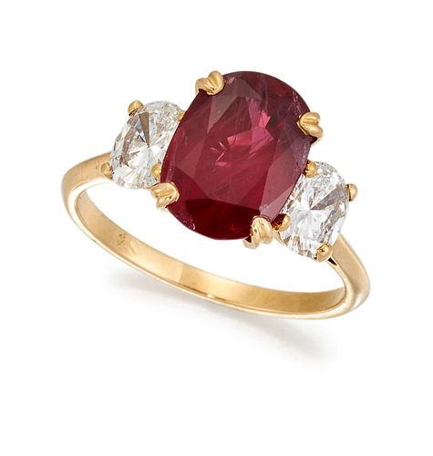A THREE STONE RUBY AND DIAMOND RING, the oval ruby, estimat