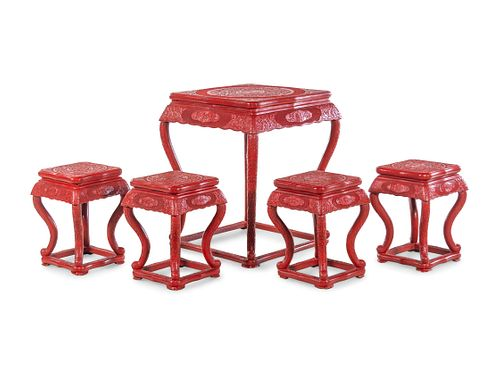 A Chinese Export Carved Red Lacquer Game Table and Four Stools