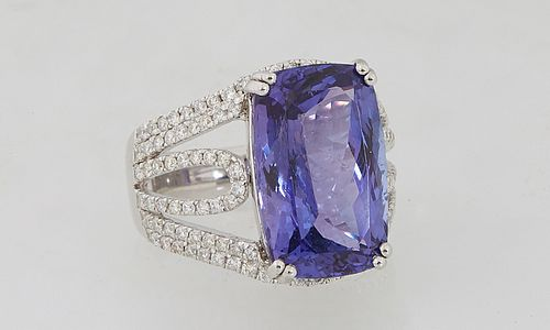 Lady's Platinum Dinner Ring, with a 13.97 carat emerald cut tanzanite atop pierced diamond mounted shoulders of the band, total diamond weight- 1.02 c
