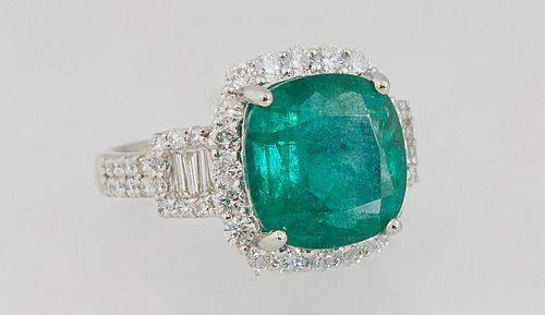 Lady's Platinum Dinner Ring, with a 6.59 carat cushion cut emerald atop a border of round diamonds, flanked by baguette and round diamond lugs over di