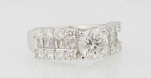 Lady's Platinum Dinner Ring, with a central round 1.54 carat diamond flanked by shoulders with a band of baguette diamonds, flanked by edge rows of ro