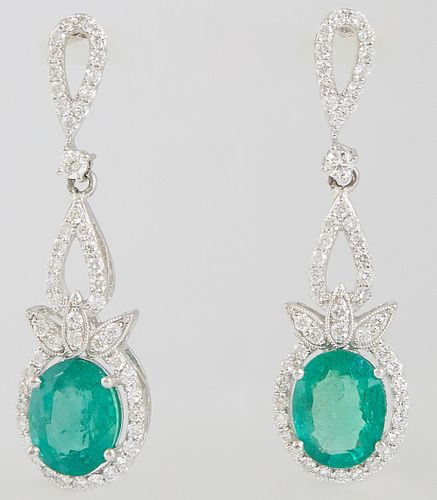 Pair of Platinum Pendant Earrings, the pear shaped studs mounted with diamonds to a pear shaped bail atop an oval pendant with a 3.11 carat oval emera