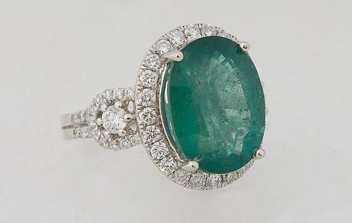 Lady's Platinum Dinner Ring, with an oval 8.13 carat emerald atop a border of small round diamonds, flanked by diamond mounted pierced lugs and diamon