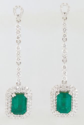 Pair of 18K White Gold Pendant Earrings, the pear shaped diamond mounted stud over a 9 round diamond chain to a pendant 3.28 carat emerald atop a conc