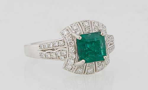 Lady's Platinum Dinner Ring, with a square 2.27 carat emerald atop a curved border of round diamonds, the tapered shoulders of the band also mounted w