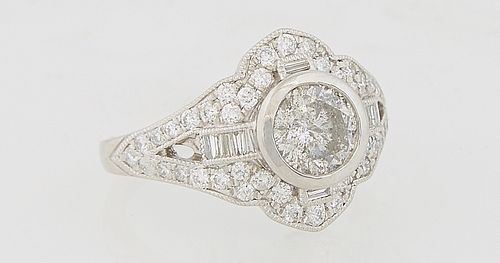 Lady's Platinum Dinner Ring, with a central 1.05 carat round diamonds flanked by baguette diamond mounted lugs and a mounted arched border of round di