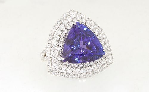 Lady's 18K White Gold Dinner Ring, with a 12.9 carat trillion cut tanzanite atop a conforming triple concentric border of round diamonds, the split sh