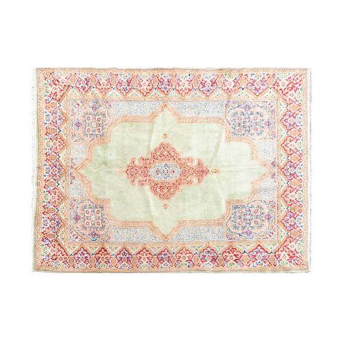 Tapete. Persia, siglo XX. Estilo Kirman. Anudado a mano en fibras de lana y algodón. Decorado con elementos florales. 352 x 261 cm