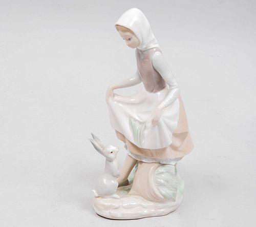 Niña con conejo. España, siglo XX. Elaborada en porcelana Lladró. Acabado brillante. Presenta fractura en la oreja del conej...