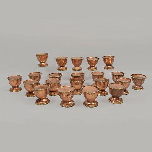 Lote de 21 hueveras. Siglo XX. Elaboradas en metal. Acabado cobre. Decoradas con elementos orgánicos en esmalte dorado.
