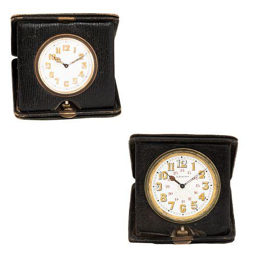 Lote de 2 relojes de viaje. Francia. Siglo XX. Elaborados en piel laqueada y latón. Con estuches y carátulas circulares.