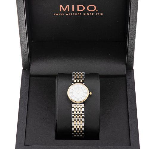 Reloj Mido. Movimiento de cuarzo. Caja circular en acero y chapa de 25 mm. Carátula color blanco con índices de números romanos.