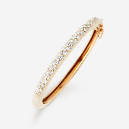 A fourteen karat gold and diamond bangle,