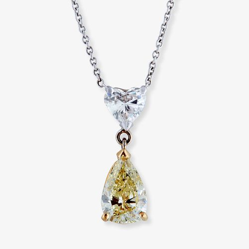 A fancy light yellow diamond, colorless diamond and fourteen karat bi-color gold pendant necklace,