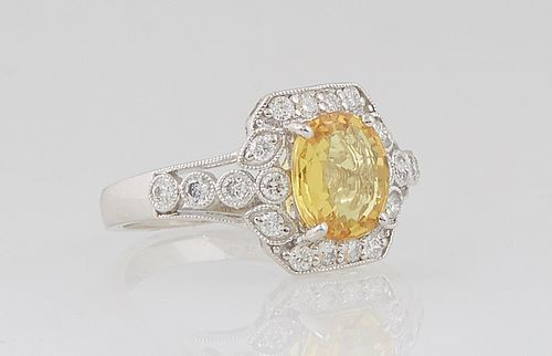 Lady's Platinum Dinner Ring, with a cushion cut 2.05 ct. yellow sapphire atop a round diamond mounted border, the shoulders of the band also mounted w