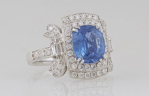 Lady's Platinum Dinner Ring, with a cushion cut 3.39 ct. blue sapphire atop a double concentric border of round diamonds, flanked by diamond mounted l
