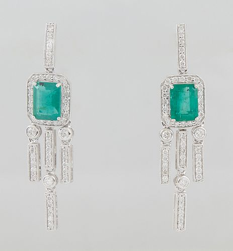 Pair of Platinum Earrings, the stud with a diamond mounted hook atop a 1.56 ct. emerald atop a border of round diamonds, suspending diamond mounted ta