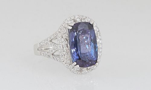 Lady's Platinum Dinner Ring, with a 7.68 ct. oval tanzanite, atop a pierced border of small round diamonds, over pierced diamond mounted shoulders of
