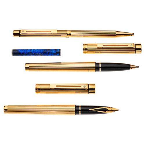 Pluma fuente, bolígrafo y lapicero Sheaffer modelo Targa. Cuerpo en acero dorado. Punto en oro amarillo de 14k. Estuche origin...