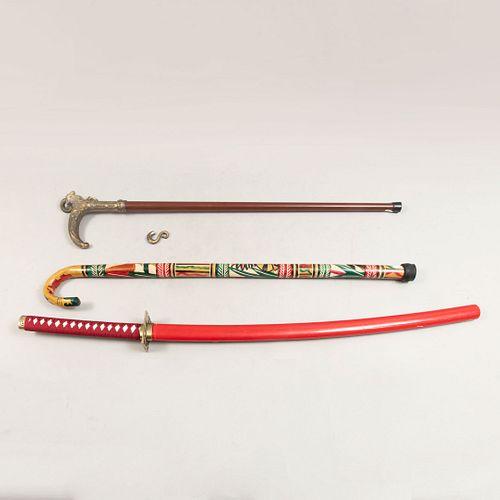 Lote mixto de 3 piezas. Diferentes orígenes y diseños. SXX En madera pirograbada, metal y acero. Consta de: katana y 2 bastones.