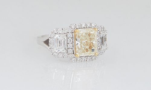 Lady's 18K White Gold Dinner Ring, with a light yellow 2.42 ct. emerald cut diamond atop a border of round diamonds, flanked by lugs with emerald cut