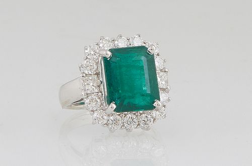 Lady's 18K White Gold Dinner Ring, with a 6.43 ct. emerald atop a border of round diamonds, total diamond wt.- 1.34 cts., Size 5 1/2, with appraisal.