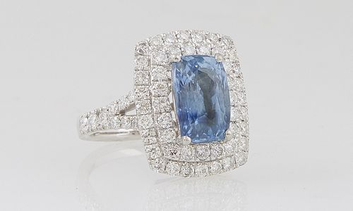 Lady's Platinum Dinner Ring, with a 4.1 ct, cushion cut natural blue sapphire, atop a double graduated concentric border of round diamonds, the split