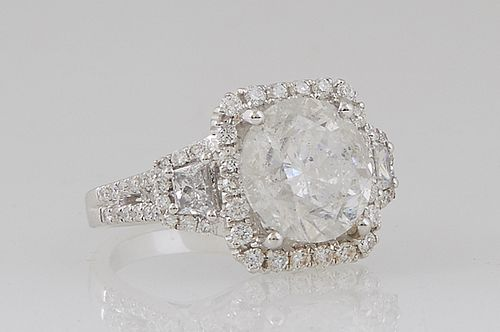 Lady's 18K White Gold Dinner Ring, with a 5.03 ct. round diamond atop a border of small round diamonds, flanked by baguette diamond lugs within diamon