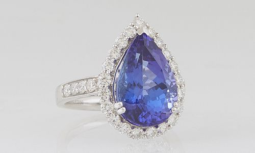 Lady's Platinum Dinner Ring, with an 8.74 ct. pear shaped tanzanite atop a conforming border of round diamonds, the shoulders of the band with graduat