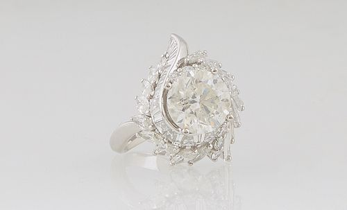 Lady's Platinum Dinner Ring, with a central 3.55 ct. round diamond atop swirled borders of baguette and round diamonds, on a split shoulder band, diam