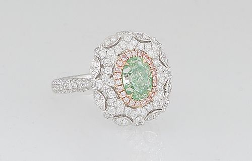 Lady's 18K White Gold Dinner Ring, with an oval 1.06 ct. green diamond, atop a border of pink diamonds, and an outer pierced scalloped border of round