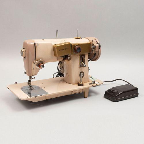 Máquina de coser. México. Siglo XX. Elaborada en metal. Marca Singer. Con pedal. Decorada con esmalte dorado. 28 cm altura
