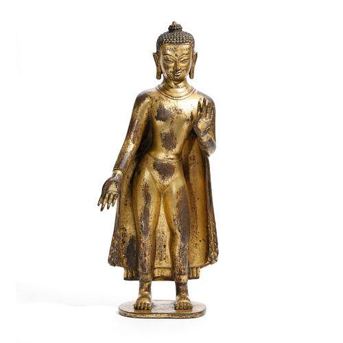 A GILT-BRONZE FIGURE OF STANDING BUDDHA, TIBET