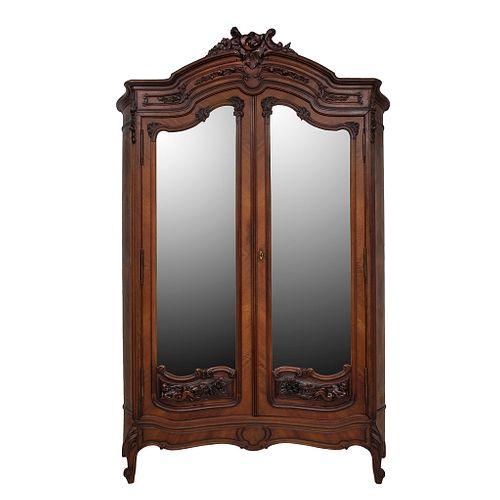 Armario.  Francia.  Siglo XX.  En talla de madera de nogal.  Con 2 puertas abatibles con espejos de lunas irregulares.